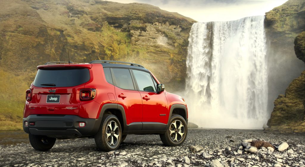 A red 2021 Jeep Renegade subcompact SUV parked next to a waterfall