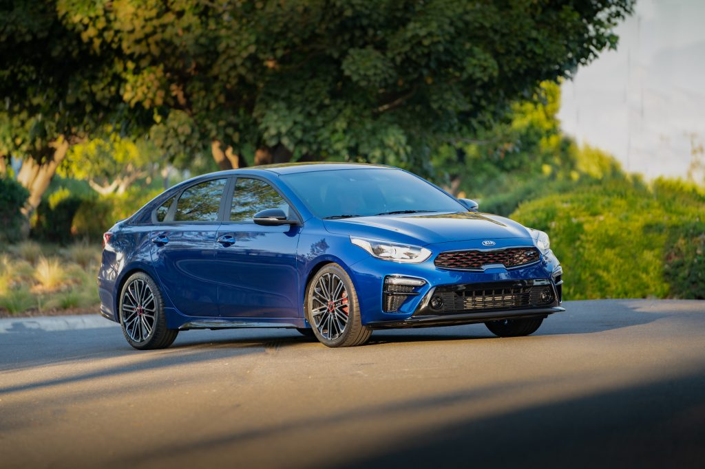 A blue 2021 Kia Forte GT Sport compact sedan parked on a paved road in front of green foliage