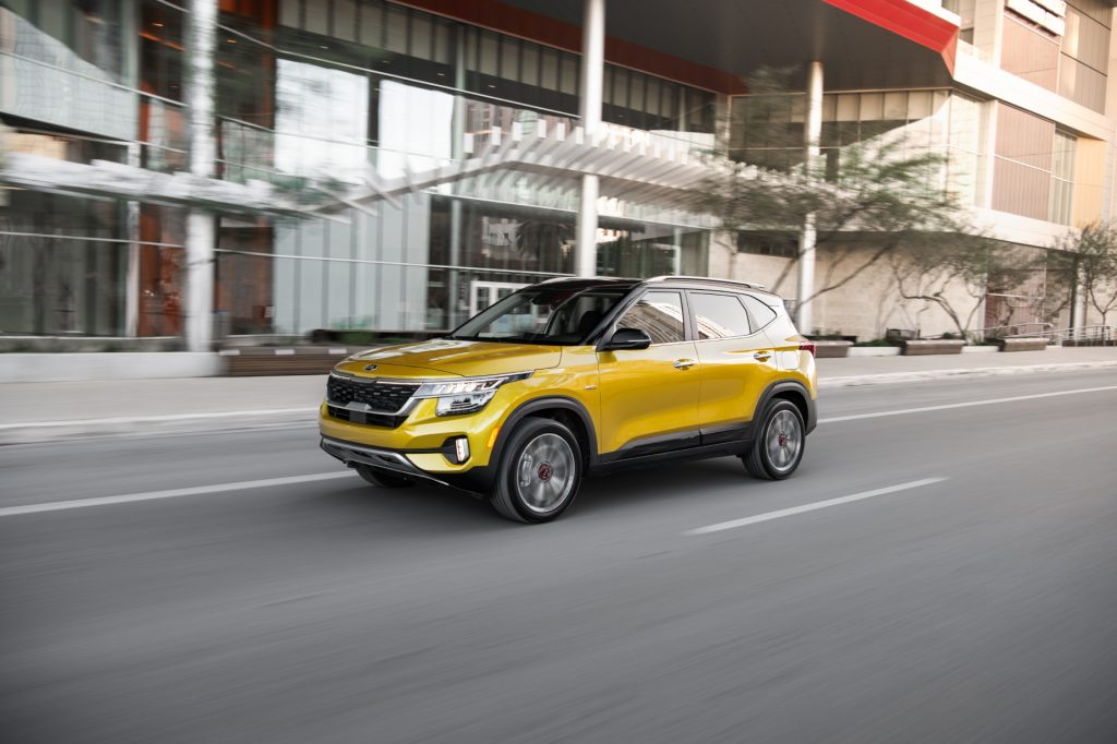 A gold 2021 Kia Seltos small SUV driving down a city road