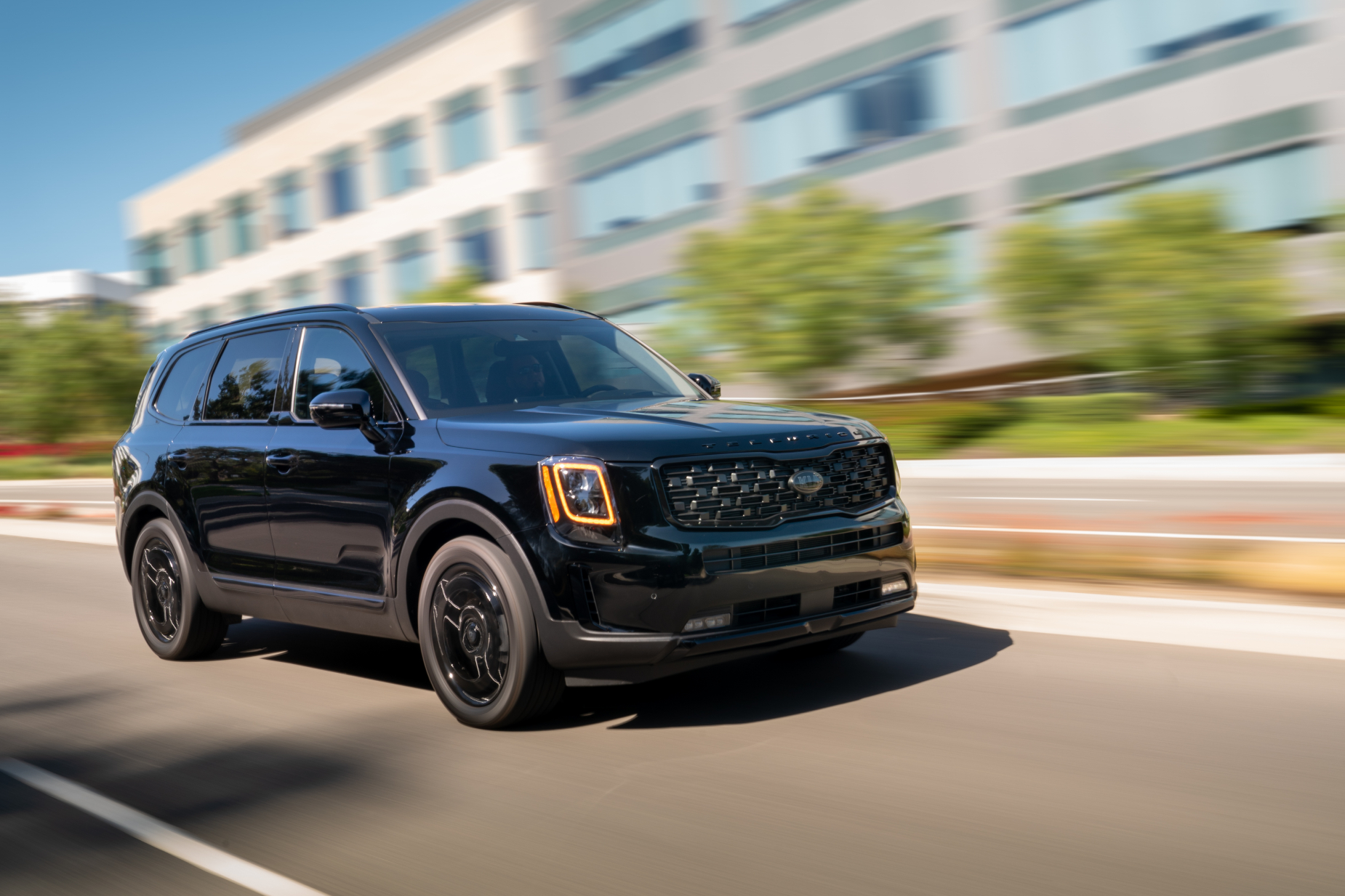 a blacked out 2021 kia telluride SUV driving on the road in the city