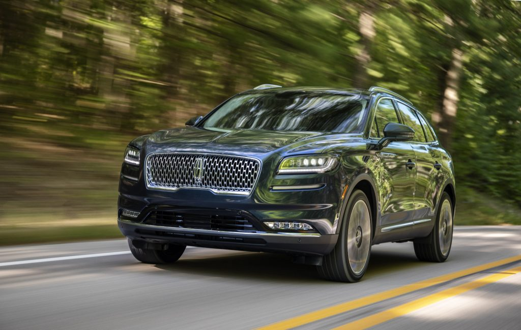 A 2021 Lincoln Nautilus in Flight Blue travels on a two-lane paved road lined by foliage
