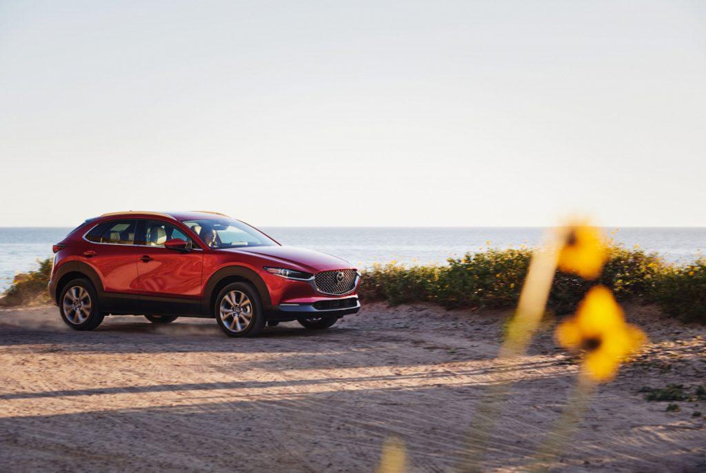 A red 2021 Mazda CX-30 overlooks an ocean