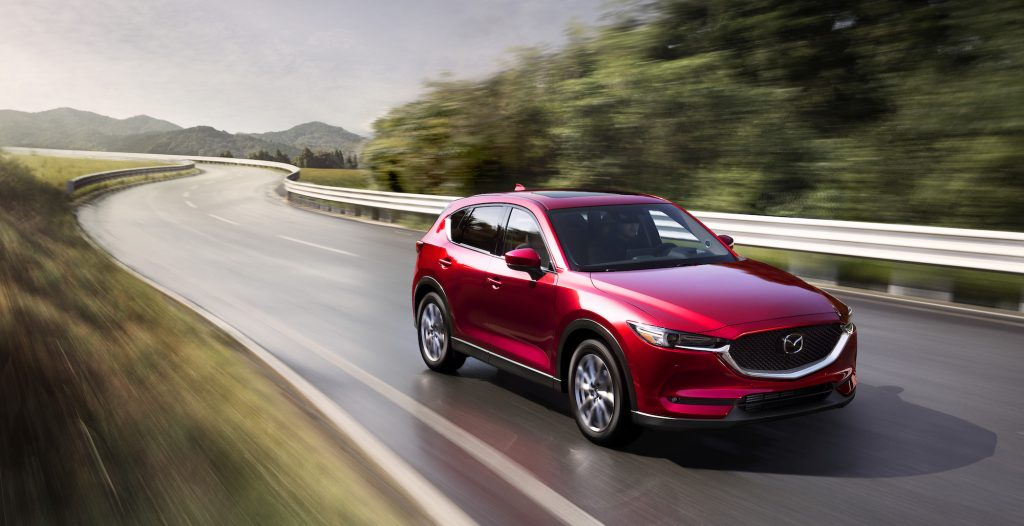 A metallic red 2021 Mazda CX-5 travels on a wet two-lane highway lined by metal guardrails and green mountains
