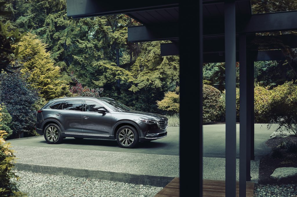 A metallic dark-gray 2021 Mazda CX-9 midsize crossover SUV sits in a home's driveway