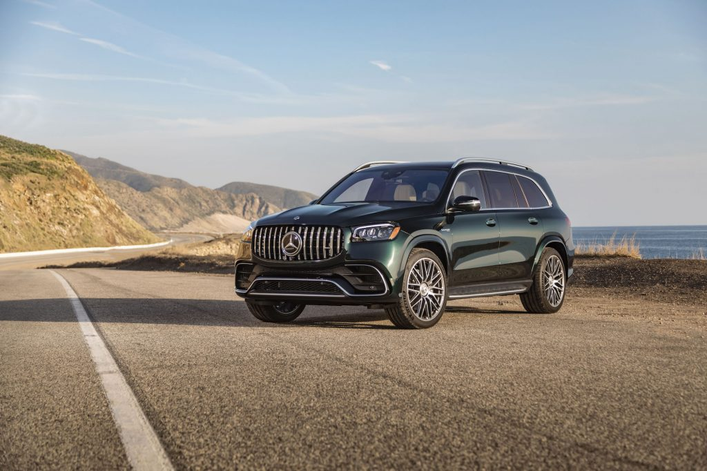 A dark-green 2021 Mercedes-AMG GLS 63 parked on a paved road with blue sky and mountains in the background