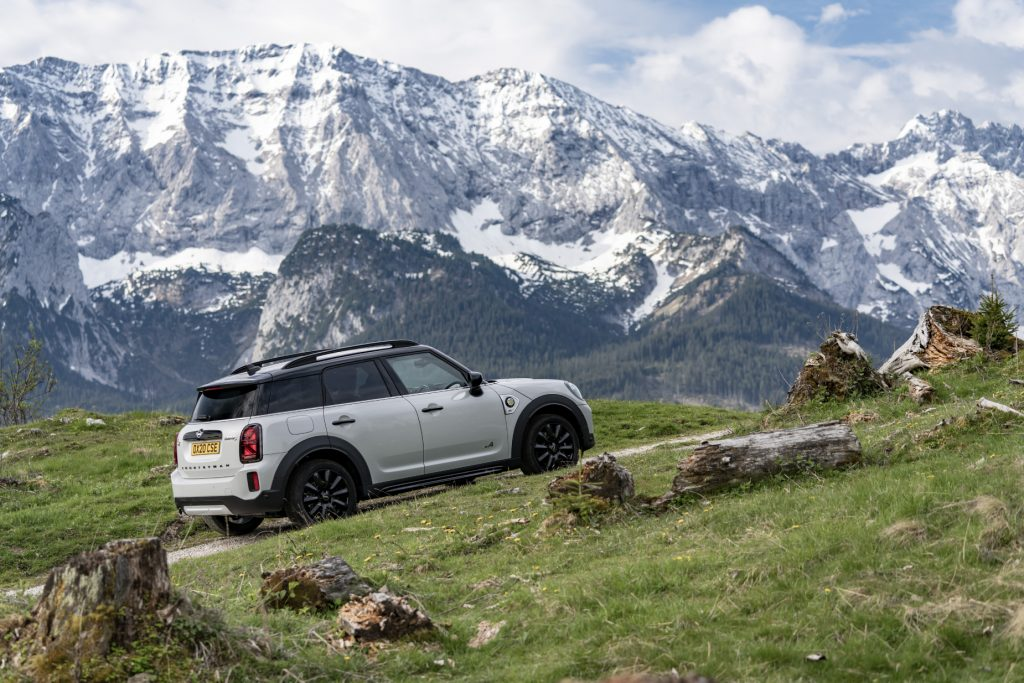 A white 2021 Mini Countryman driving uphill with a mountain in the background