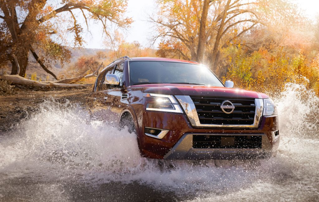 A dark-red 2021 Nissan Armada full-size SUV drives across a creek on a sunny day