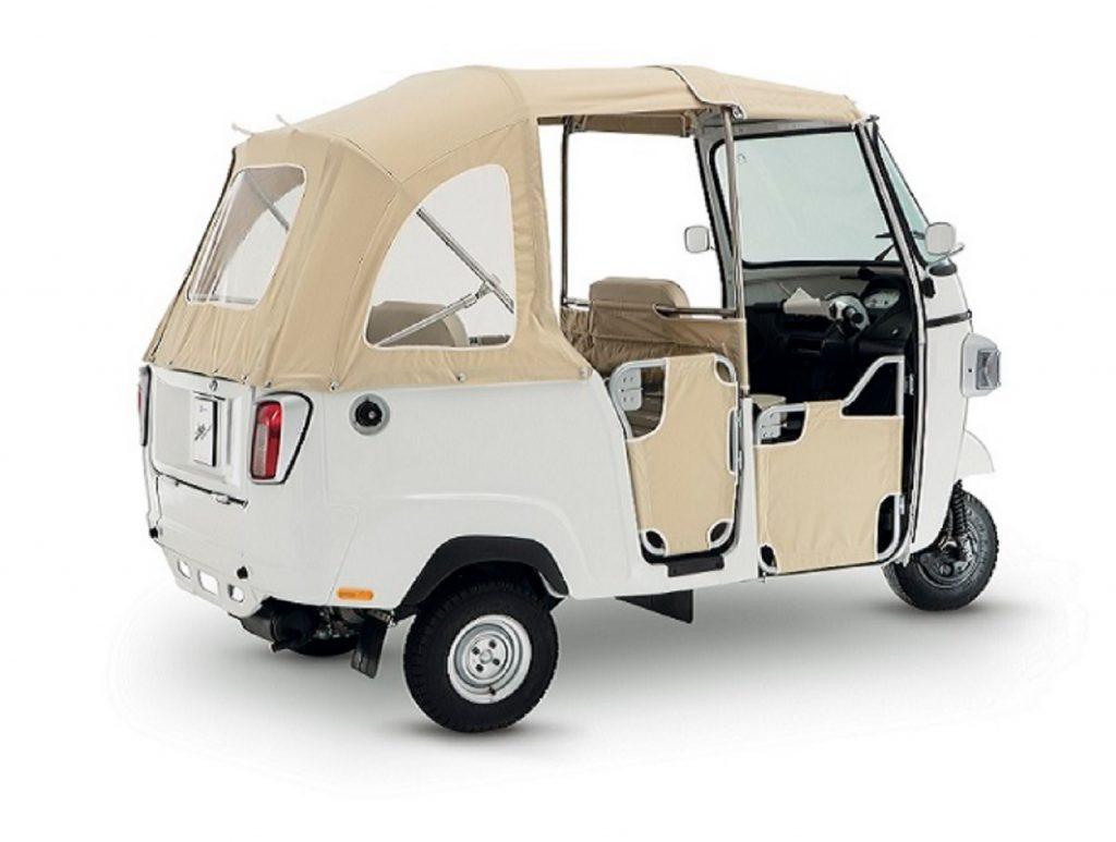 The rear 3/4 view of a tan-soft-top white 2021 Piaggio Ape Calessino