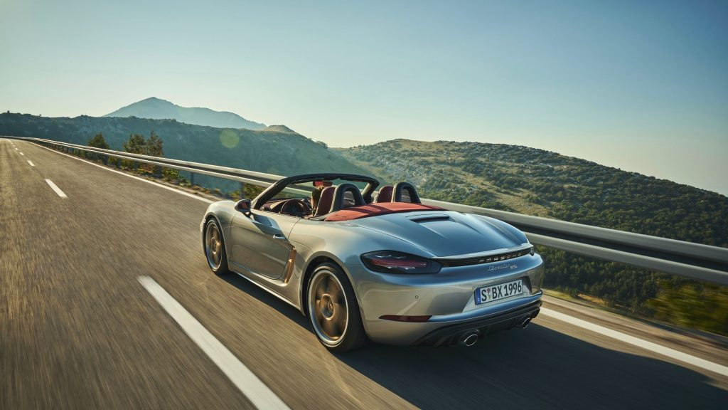 The rear 3/4 view of the silver 2021 Porsche 718 Boxster 25 Years on a mountain road