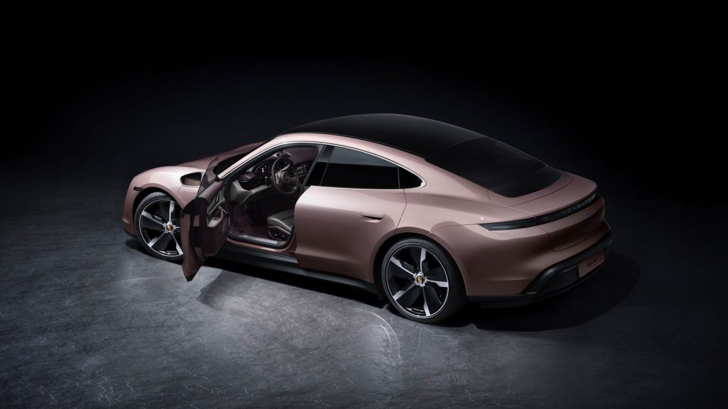 The side 3/4 view of a pink 2021 Porsche Taycan with its door open