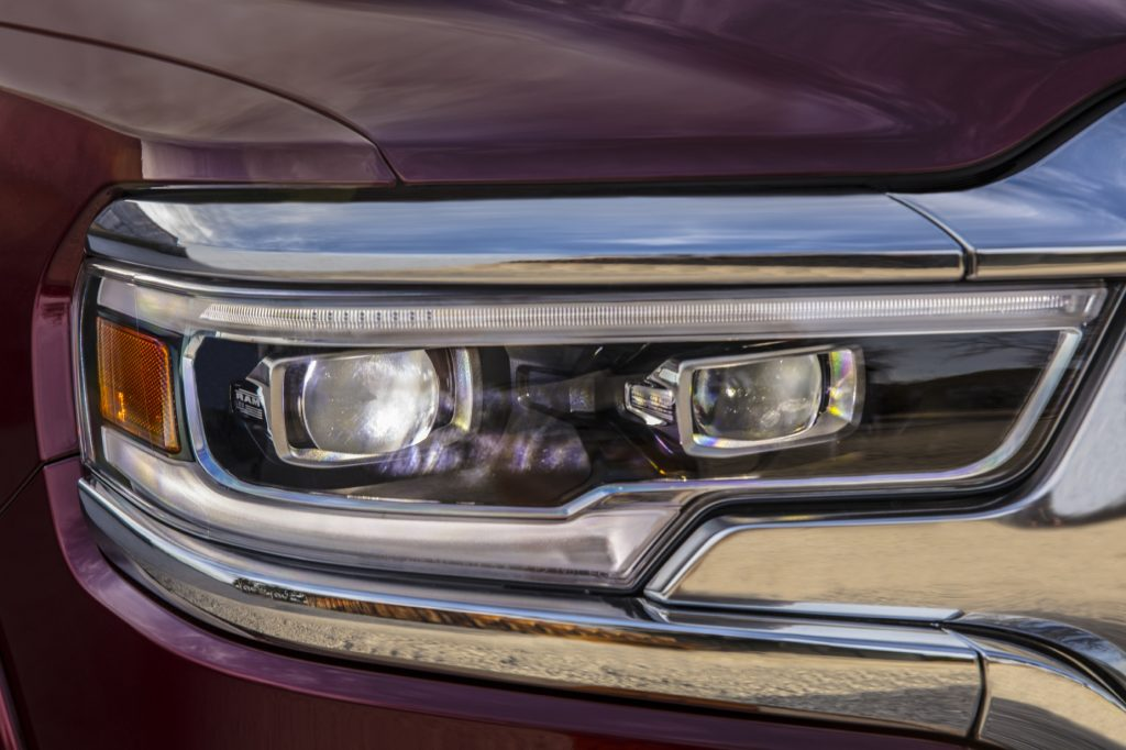 A close-up look at the headlights of a red 2021 Ram 1500 Limited