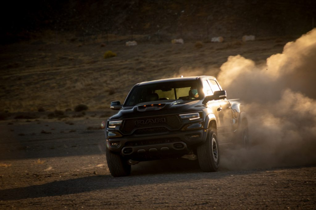A black 2021 Ram 1500 TRX driving off-road with dirt kicking up