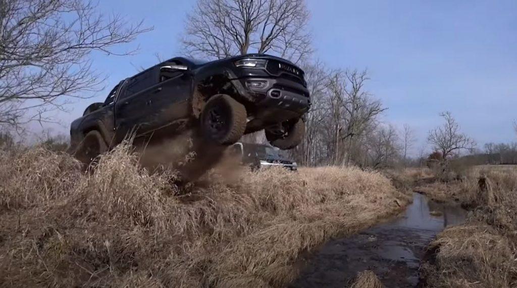 A black 2021 Ram 1500 TRX off-road pickup runs off the end of a ramp.