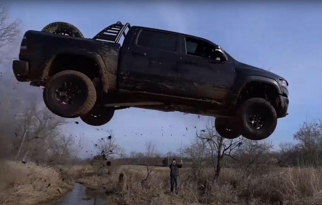 A black 2021 Ram 1500 TRX off-road pickup runs off the end of a ramp.