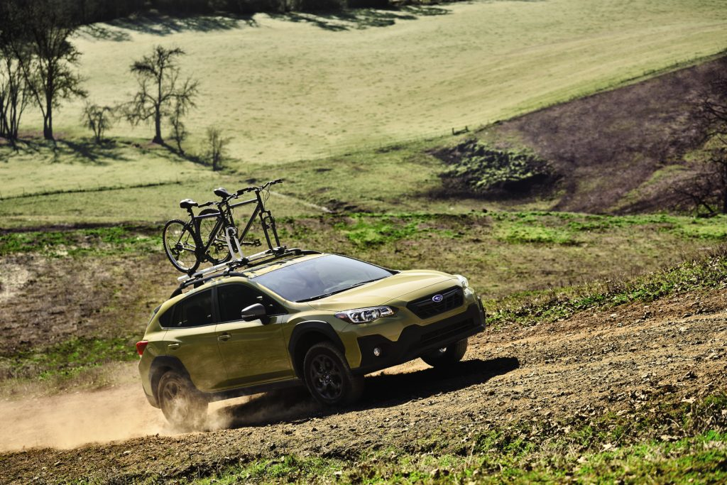 A mustard yellow 2021 Subaru Crosstrek with a bike attached to its roof rack driving down a dirt roat