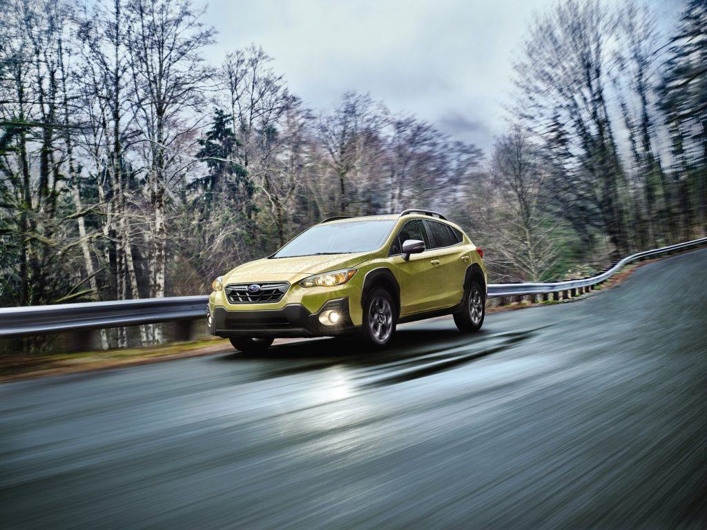 A chartreuse 2021 Subaru Crosstrek Sport Hero travels on a wet paved road along a guardrail and trees
