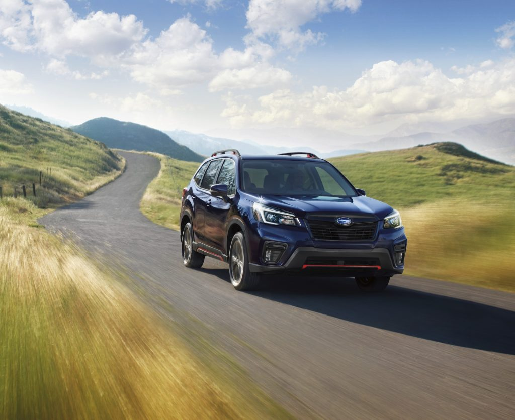 A dark-colored 2021 Subaru Forester travels on a paved road through grassy hills