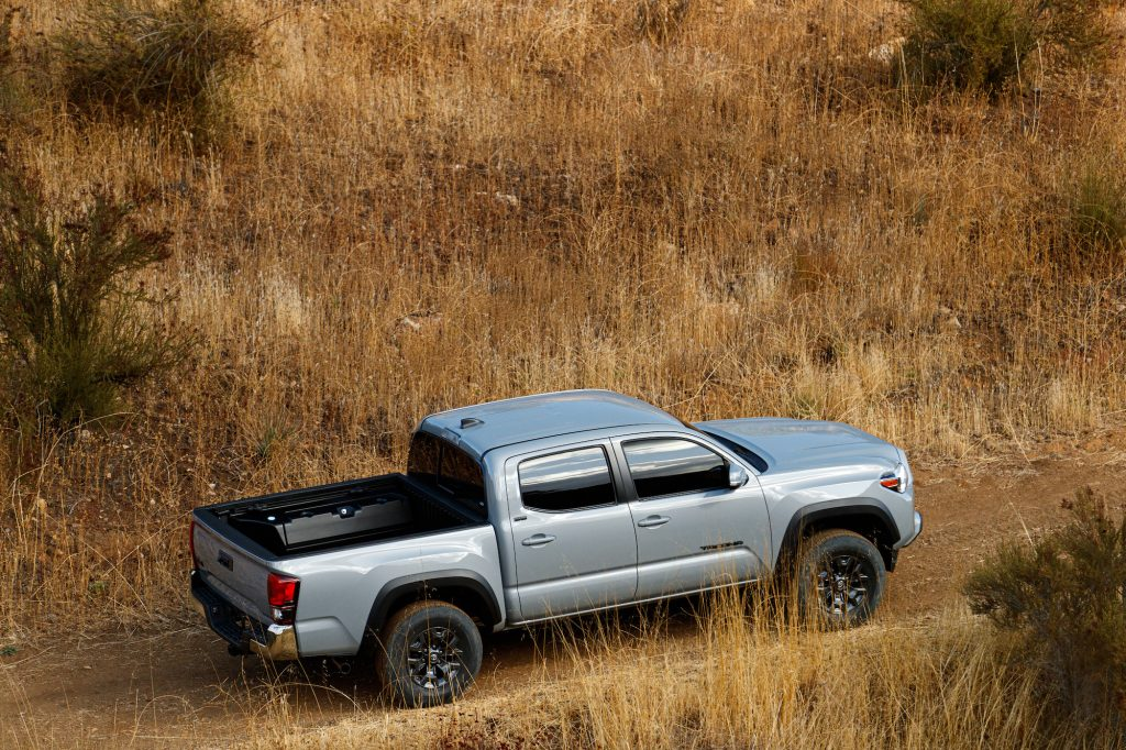 A silver 2021 Toyota Tacoma Trail Edition parked on a dirt road amid brown weeds