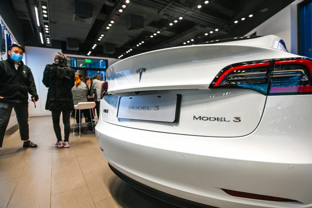 A close-up of the Tesla Model 3 on display in a small showroom