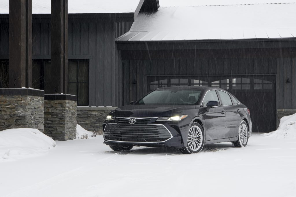 A black 2021 Toyota Avalon Limited AWD surrounded by snow in a driveway