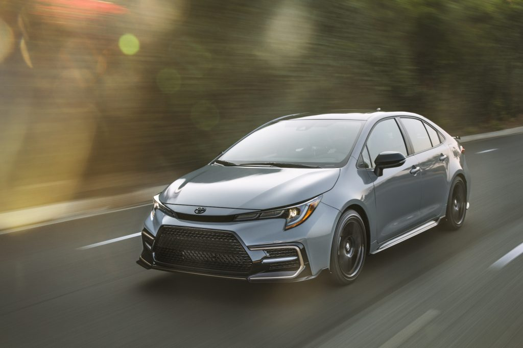 A silver 2021 Toyota Corolla Apex Edition travels on a two-lane paved road lined by foliage