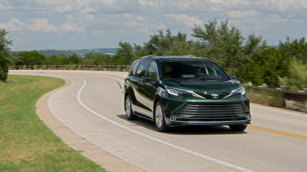 A green 2021 Toyota Sienna driving down a road