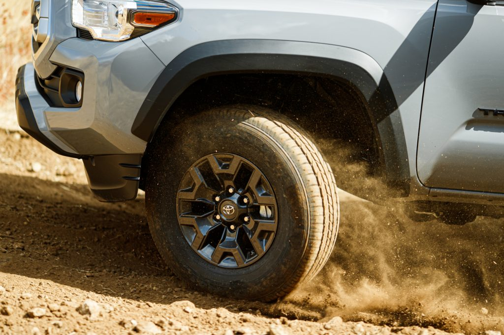 The front left tire of a 2021 Toyota Tacoma kicking up dirt while driving off-road