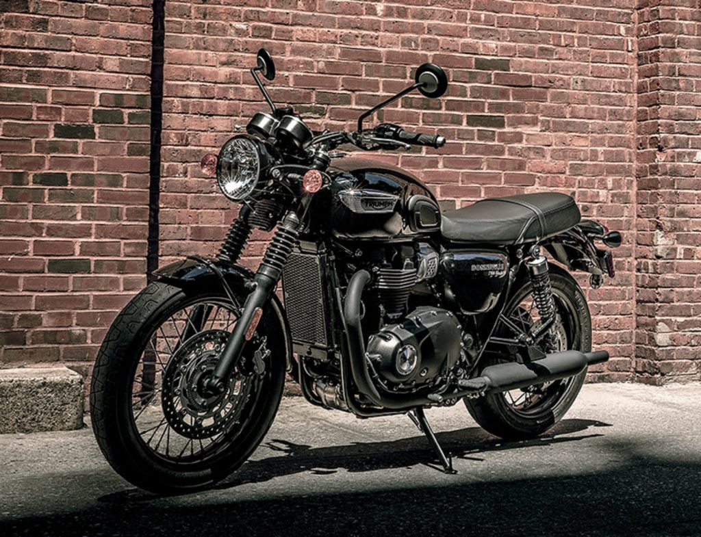 A black 2021 Triumph Bonneville T100 by a brick wall