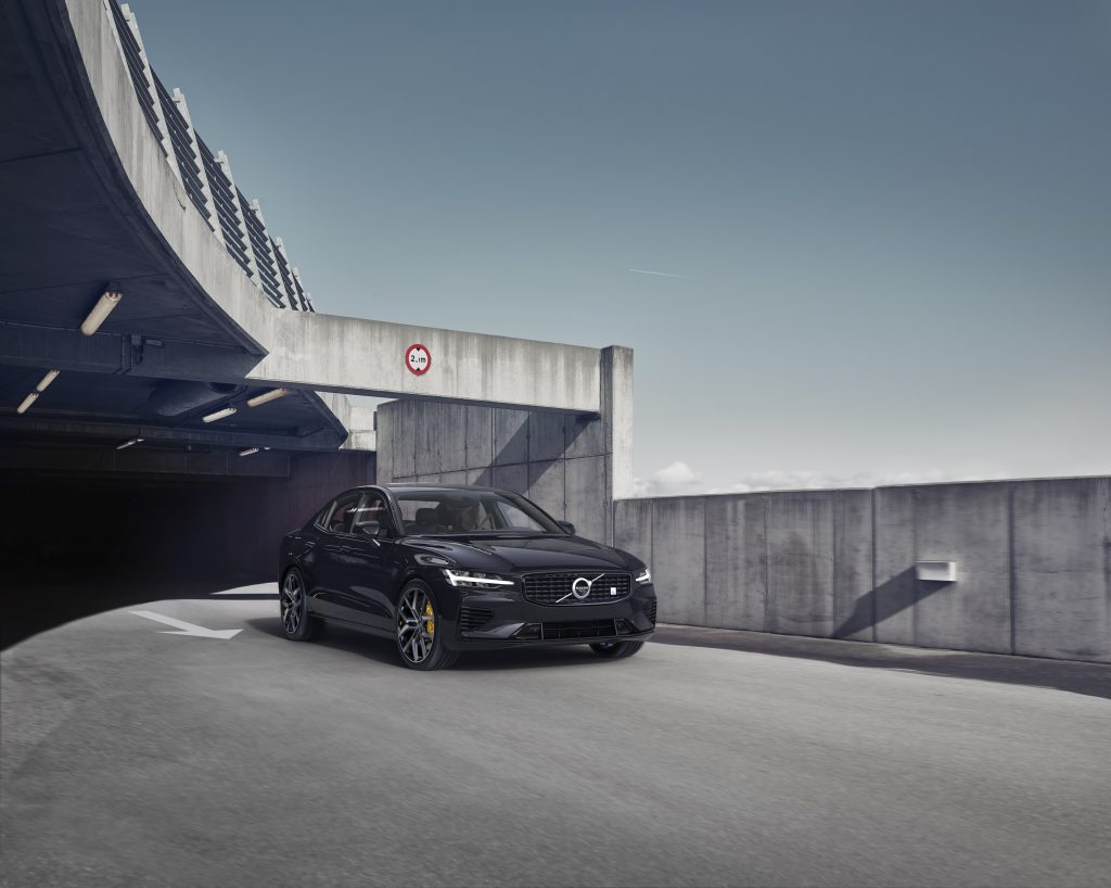 A black 2021 Volvo S60 driving on a road, emerging from the shadows