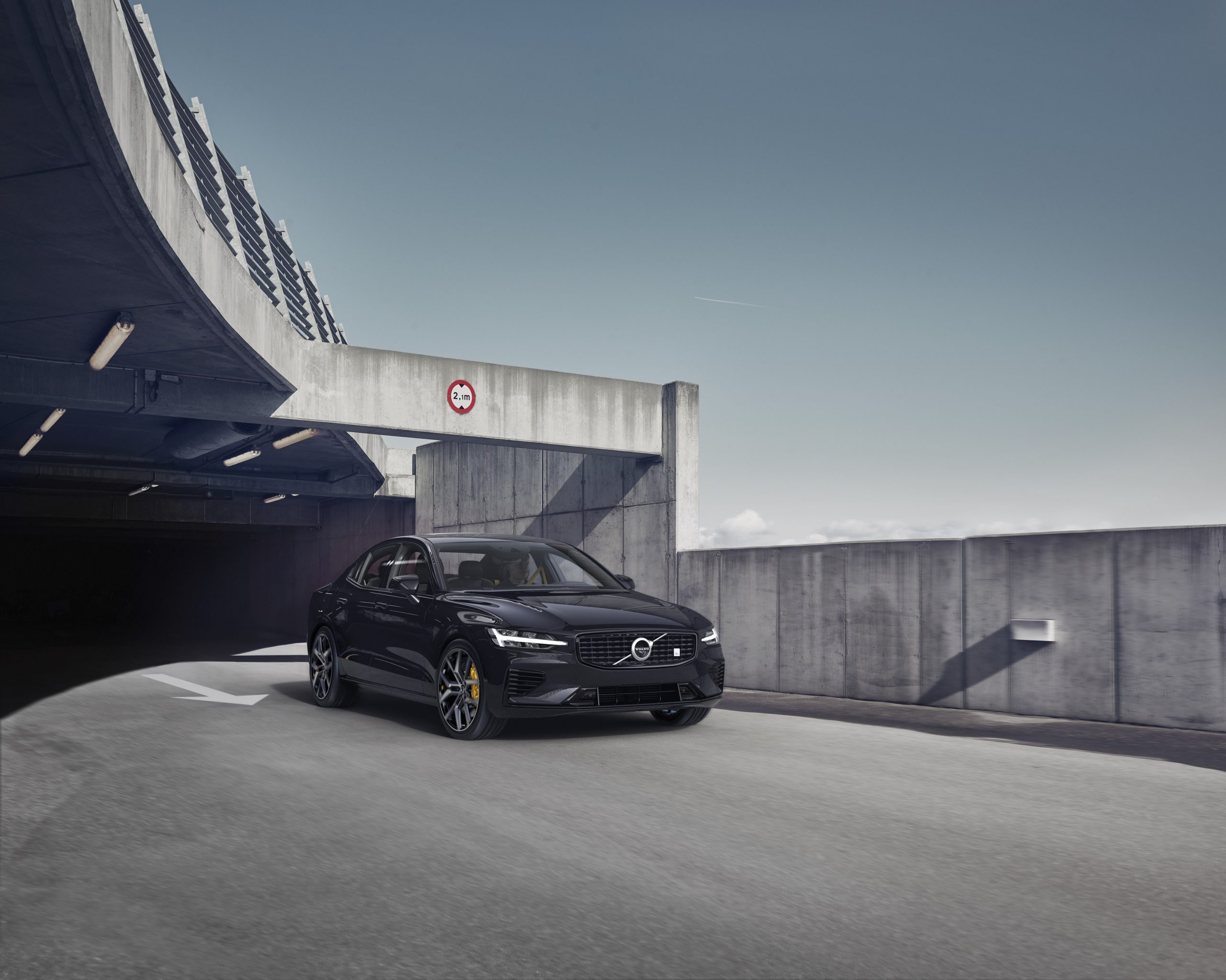 a black 2021 Volvo S60 luxury car pulling out of an upscale urban parking garage
