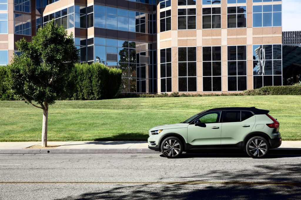 A mint and black 2021 Volvo XC40 Recharge parked on the side of the road with a tree, buldings, and grass in the background