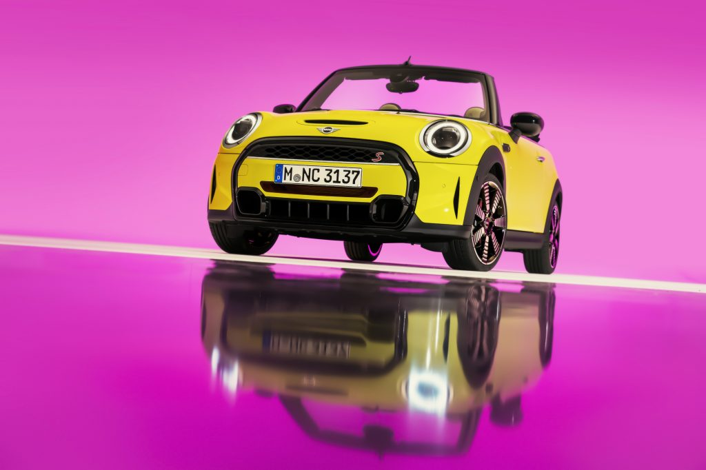 A yellow 2022 Mini Cooper S Convertible on display with a pink background