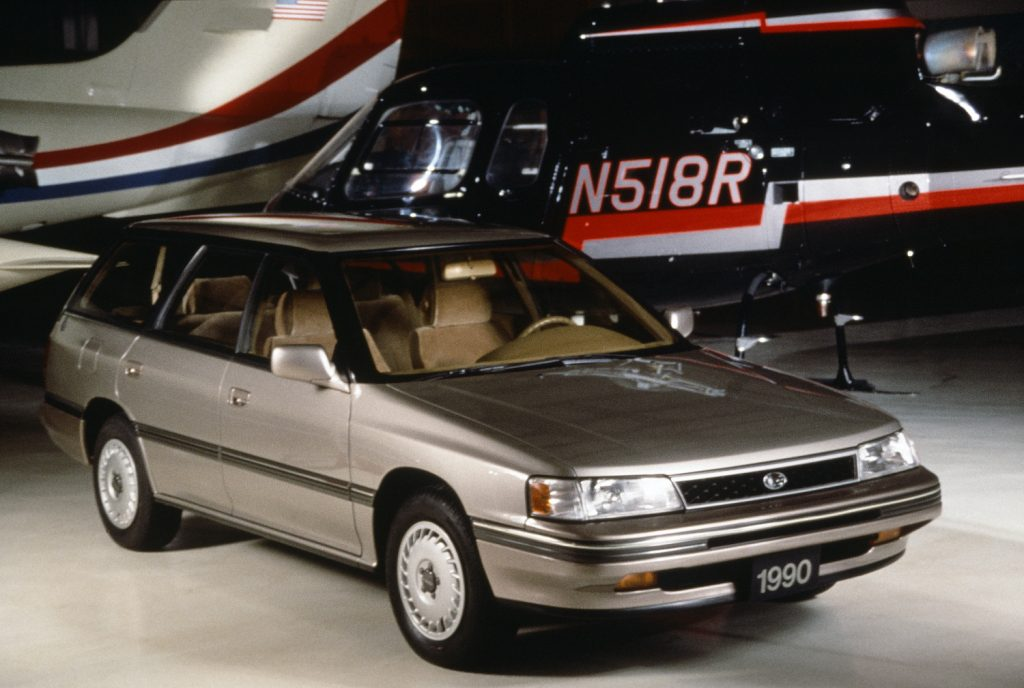 1990 Subaru Legacy wagon parked in front of a plane