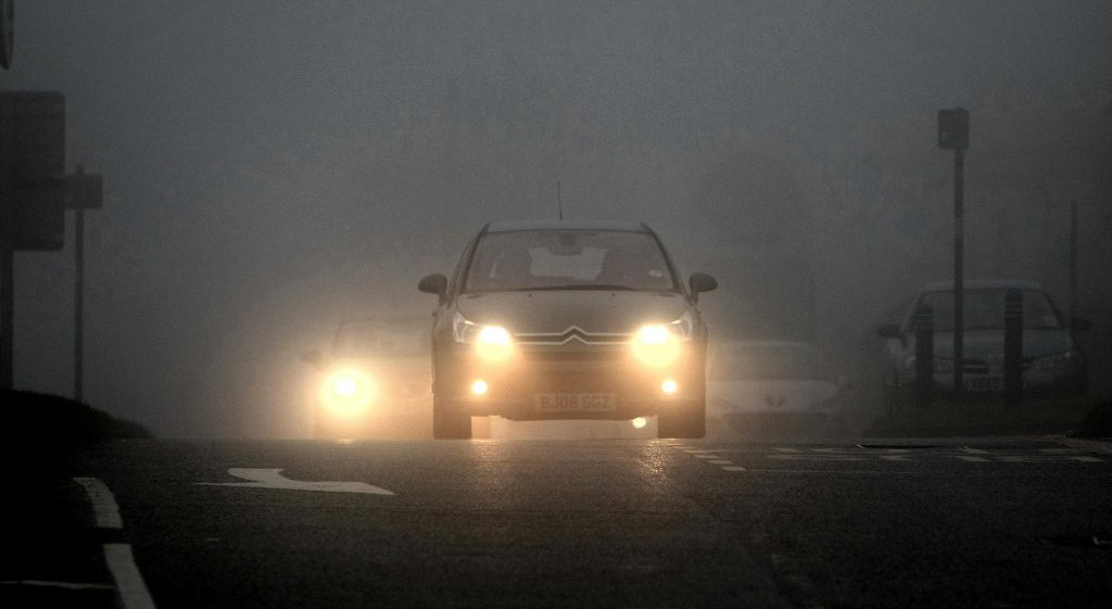 A Citroen with its fog lights on drives on a foggy British roadway