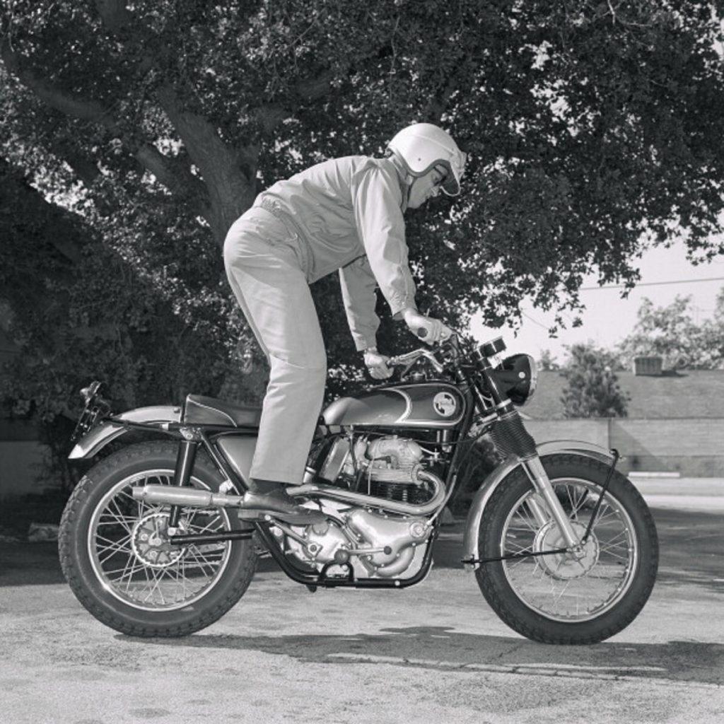 A rider using the kickstarter on a 1967 Norton P11 motorcycle