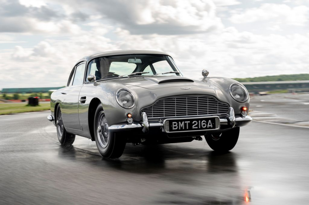 A silver Aston Martin DB5 Goldfinger Continuation on a wet track