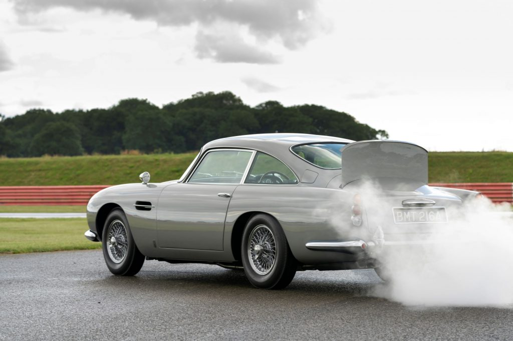 The rear view of a silver Aston Martin DB5 Goldfinger Continuation with its smokescreen and bullet-resistant shield deployed