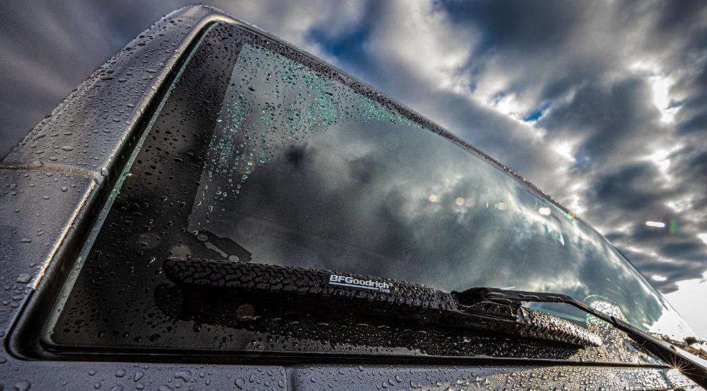 BFGoodrich Off-Road Wiper blades on a rain-streaked gray-blue Jeep Wrangler