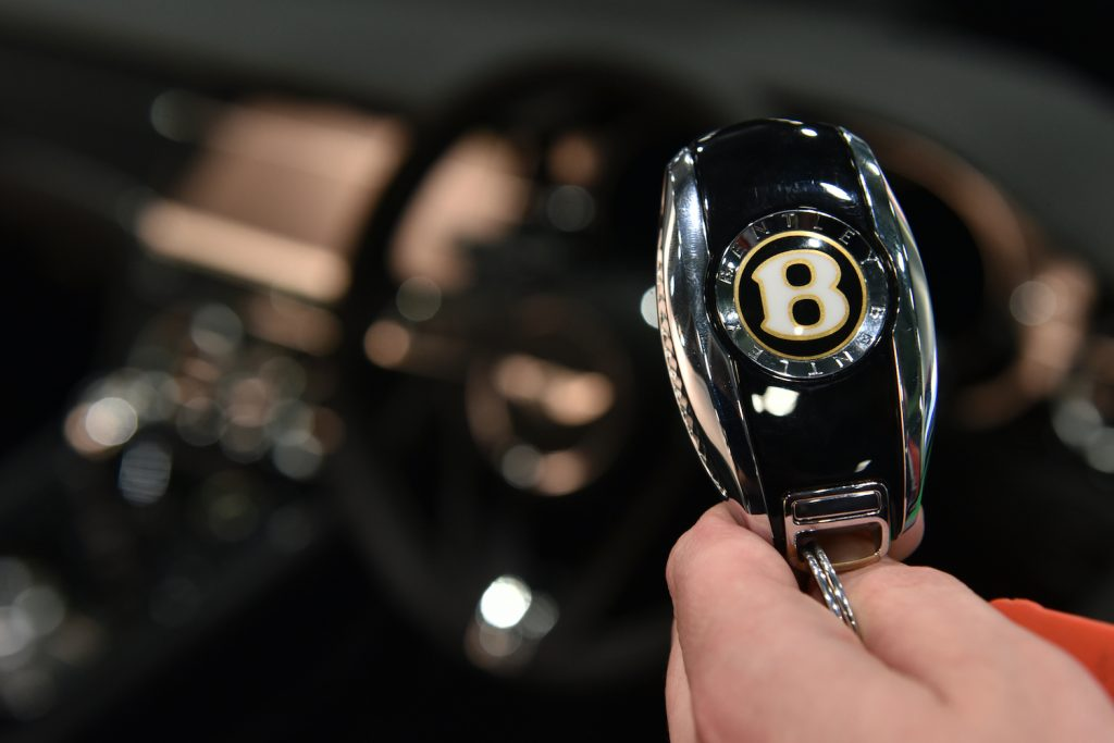 A Bentley key fob in someone's hand