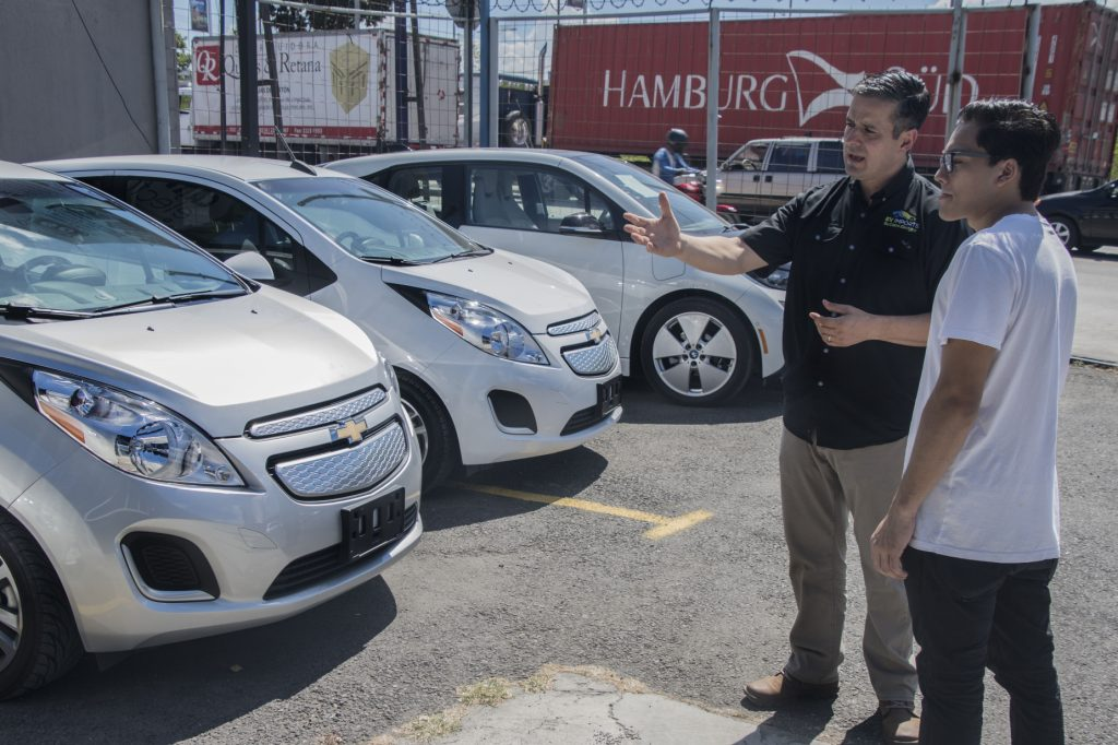 A salesman talking to a customer about new cars and used cars while next to Chevrolet models