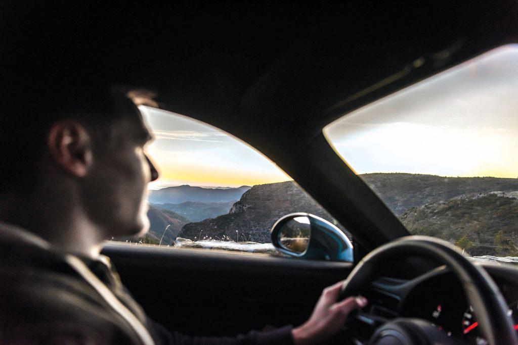 A young man driving a car through the mountains