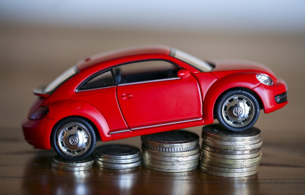 A visual of an auto loan, represented by a red toy Volkswagen bug parked on four ascending stacks of silver coins
