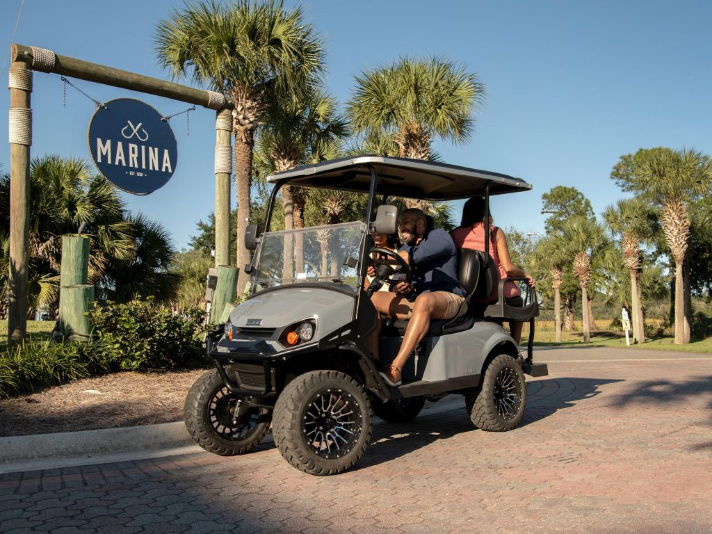 A gray golf cart headed to a marina