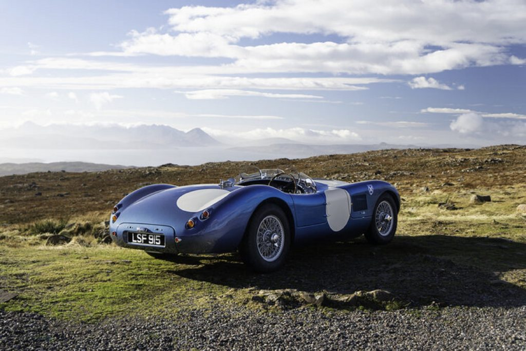 The rear 3/4 view of a blue-and-white Ecurie Ecosse LMC