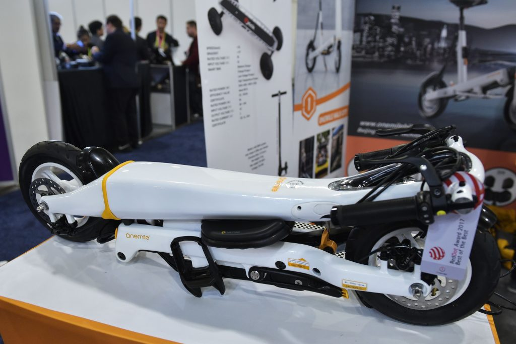 A white folding electric scooter is on display.