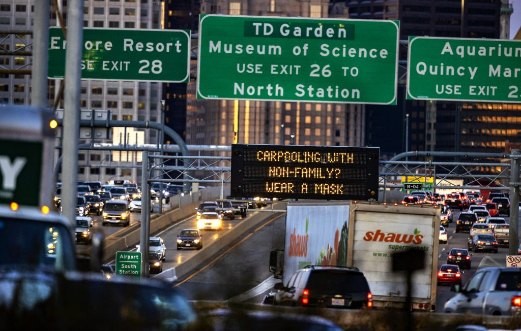 An image of several cars in traffic on a highway with a COVID-19 message on a large sign.