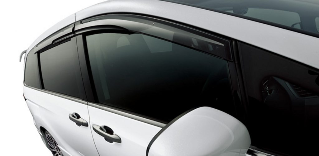 A close-up of a white JDM 2021 Honda Odyssey with Mugen window guards and a white rear spoiler