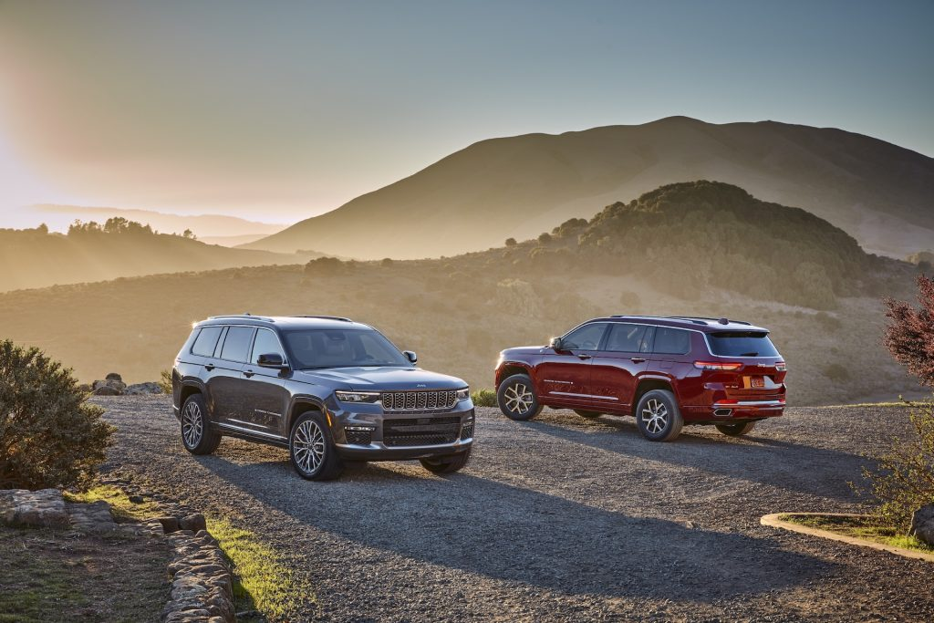 A gray-brown 2021 Jeep Grand Cherokee L Summit Reserve and a red Overland on a foggy hill