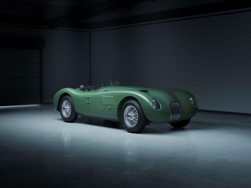 A green Jaguar C-Type Continuation in a hangar