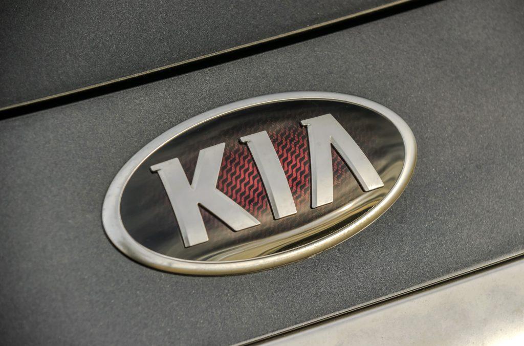 A close-up look at the Kia Logo on a black 2020 Kia K900